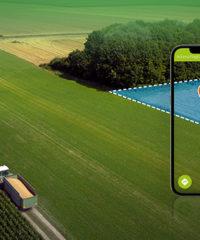 Traktor mit Navigationspfeil und Smartphone mit Navigationspunkt am Feld